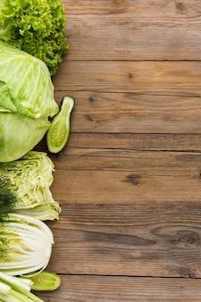 Surtido de verduras vista superior sobre fondo de madera con espacio de copia
