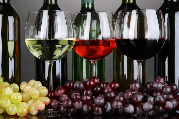 Surtido de vino en vasos y botellas en gris