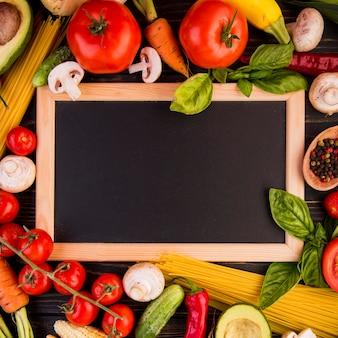 Surtido de vista superior de diferentes verduras con pizarra vacía