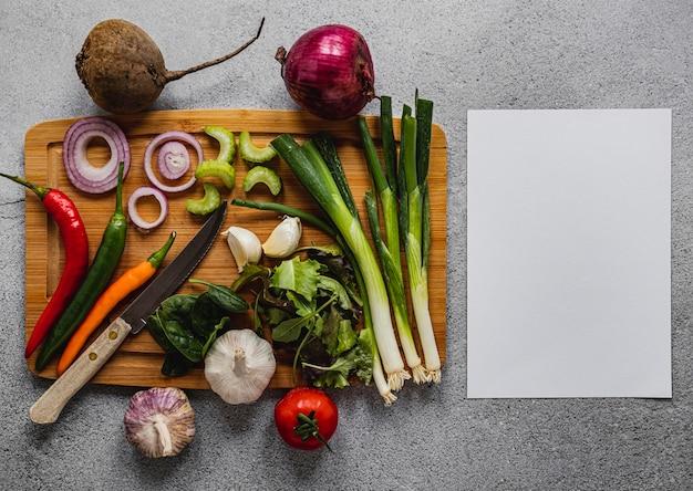 Surtido de vista superior de verduras y papel en blanco