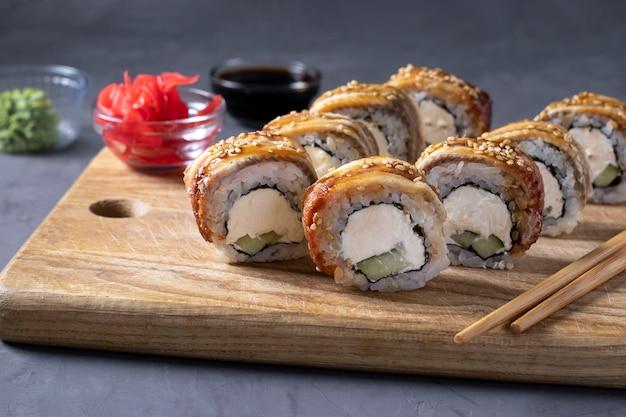 Sushi con anguila ahumada y queso philadelphia sobre tabla de madera sobre fondo gris. comida sana. de cerca