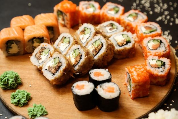 Sushi con atún, salmón, verduras, jengibre, wasabi, vista lateral