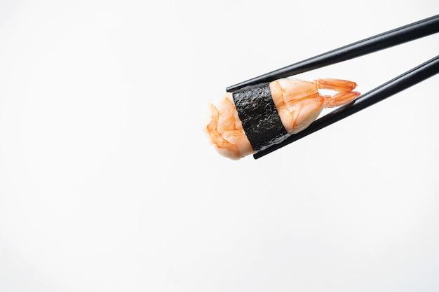Sushi del camarón en palillo de la tienda en fondo blanco aislado