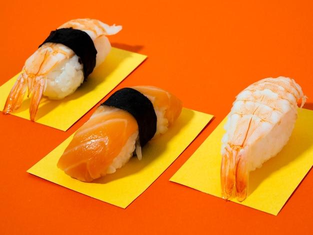 Sushi de camarones y salmón sobre fondo naranja