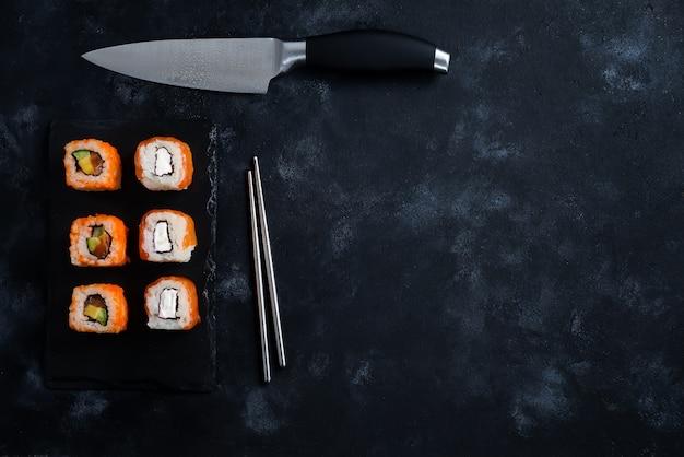 Sushi diferente servido en un plato de pizarra negro con cuchillo japonés y palillos de metal