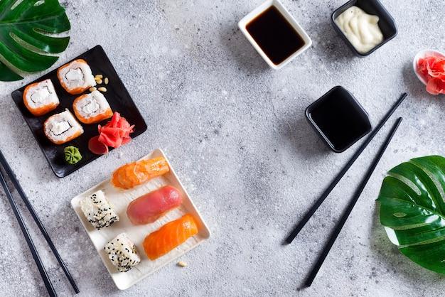 Sushi fresco en pizarra blanco y negro con palos de metal, salsa y hojas verdes