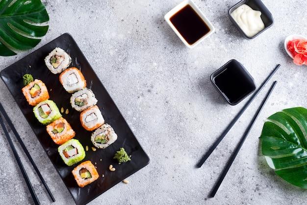 Sushi fresco en pizarra negra con palitos de metal, salsa y hojas verdes