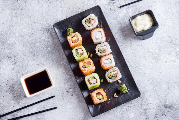 Sushi fresco en pizarra negra con palos de metal, salsa en piedra