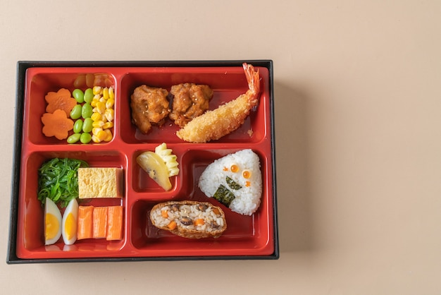 (sushi inari) arroz de sushi envuelto en tofu seco con camarones fritos y pollo frito en un juego de bento - estilo de comida japonesa