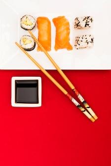 Sushi japonés fresco con pescado de salmón en bandeja con salsa de soja y palillos de madera
