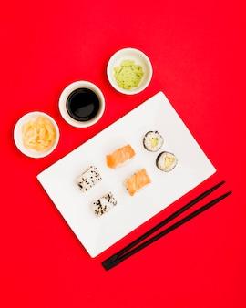 Sushi japonés con salsa de soja; jengibre y wasabi sobre fondo rojo