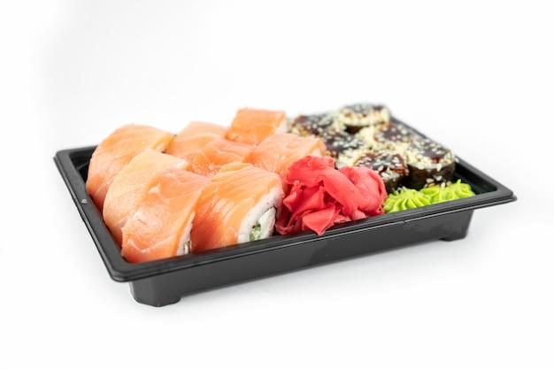 Sushi para llevar en envases de plástico, rollos de filadelfia y unagi maki, salsa de soja, jengibre rosado, wasabi, concepto de entrega de sushi
