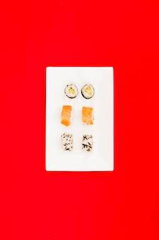 El sushi maki con salmón y filadelfia ruedan en una bandeja blanca sobre una superficie roja brillante