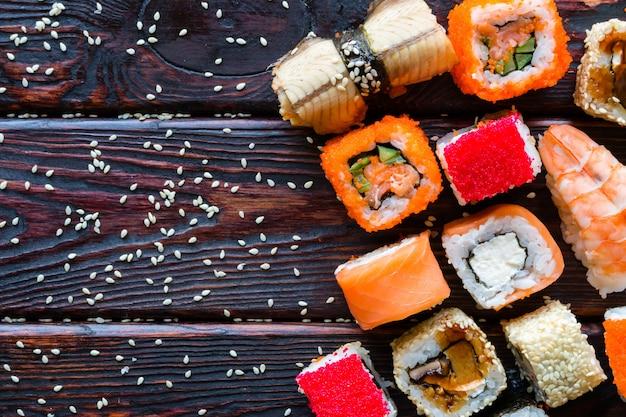 Sushi, nigiri y rollos de diferentes gustos sobre un fondo negro y espacio para texto