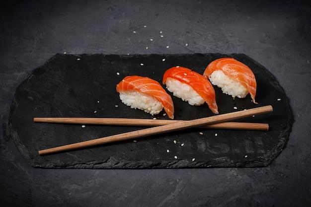Sushi nigiri tradicional japonés con salmón, sobre una pizarra de piedra negra, horizontal