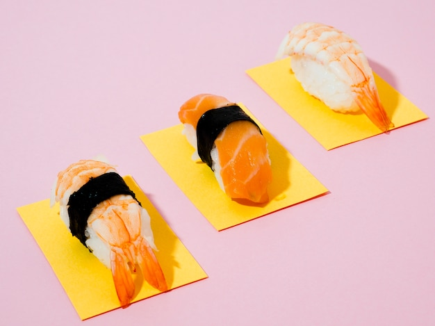 Sushi en papeles amarillos sobre fondo rosa