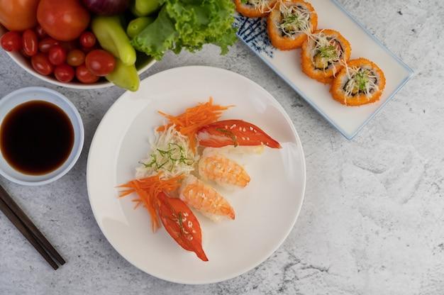 El sushi está en un plato con palillos y salsa en un piso de cemento blanco.