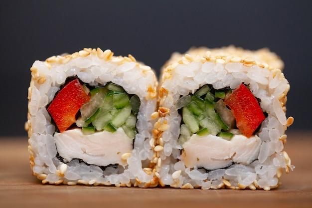 Sushi roll con salmón, queso y cucumbas.