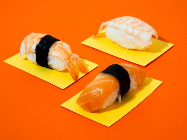Sushi de salmón y camarones sobre fondo naranja