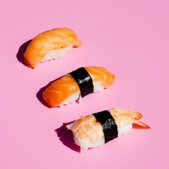 Sushi de salmón y camarones sobre fondo rosa