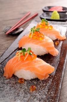 Sushi de salmón con caviar en una fila