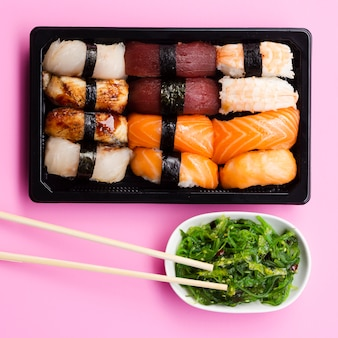 Sushi set box con ensalada de algas sobre un fondo rosa