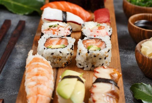 Sushi set nigiri y rollos de sushi en una bandeja de madera cerrar
