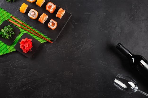 Sushi set de sashimi y rollos de sushi, botella de vino y una copa servida en pizarra de piedra.