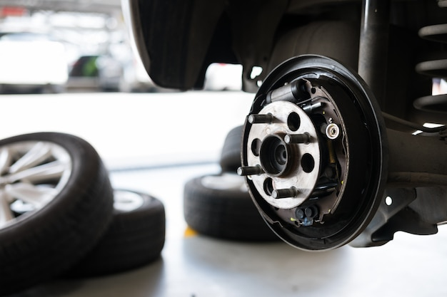 Suspensión y cojinete del cubo de la rueda en el servicio de mantenimiento de automóviles. carro elevador por hidráulico, a la espera de reemplazo de llantas en garaje. concepto de rueda perforada