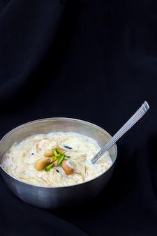 Sweet kheer o khir payasa o sheer khurma seviyan - famoso postre indio con leche y arroz o fideos. vertical. copia espacio