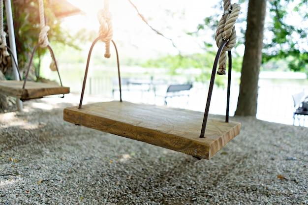 Swing en el patio de recreo en el parque público con puesta de sol