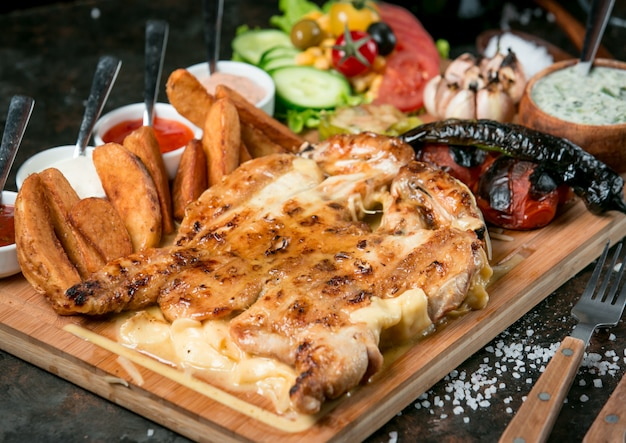 Tabaka de pollo frito en el horno sobre tabla de madera