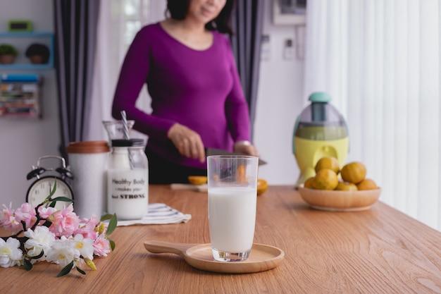 Tabla de cocina con el vidrio de leche en la mujer que corta el fondo de las frutas.