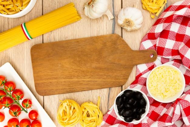 Tabla de cortar con aceitunas y pasta.