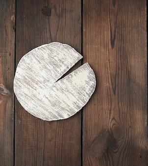 Tabla de cortar blanca redonda sobre una superficie de madera marrón