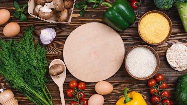 Tabla de cortar circular con verduras frescas en la mesa