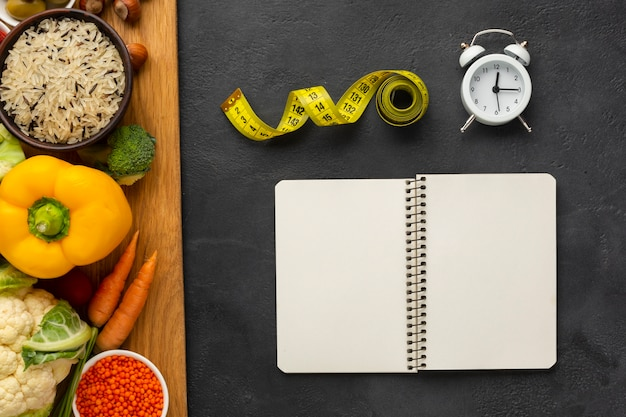 Tabla de cortar con comestibles y maqueta de cuaderno