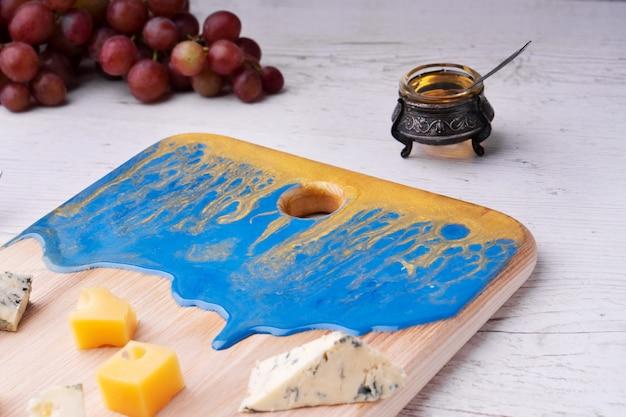 Tabla de cortar de composición con un patrón abstracto, queso, uvas de miel, flores de orquídeas