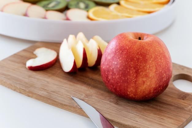 Tabla de cortar con cuchillo, manzana roja y rodajas de manzana. detrás hay un deshidratador con rodajas de naranja, kiwi y manzanas.
