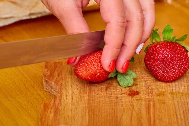 En la tabla de cortar hay varias fresas maduras y jugosas, una de ellas cortada con un cuchillo de acero en manos de una mujer.