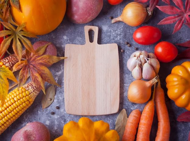 Tabla de cortar con hojas de otoño y verduras en el fondo negro