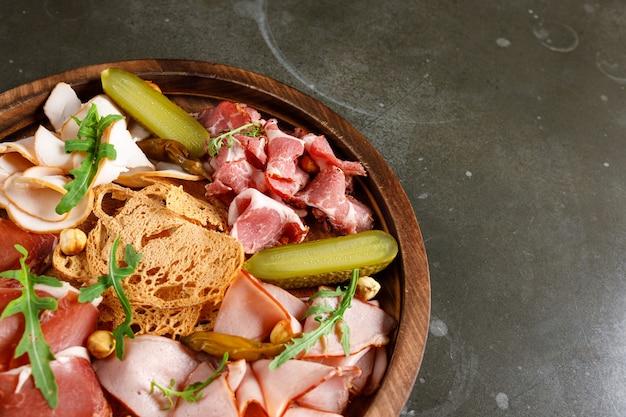 Tabla de cortar con jamón, salami, queso, palitos de pan y aceitunas sobre fondo de piedra oscura. desde la vista superior