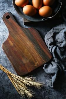 Tabla de cortar de madera en blanco y huevos y trigo seco sobre fondo oscuro