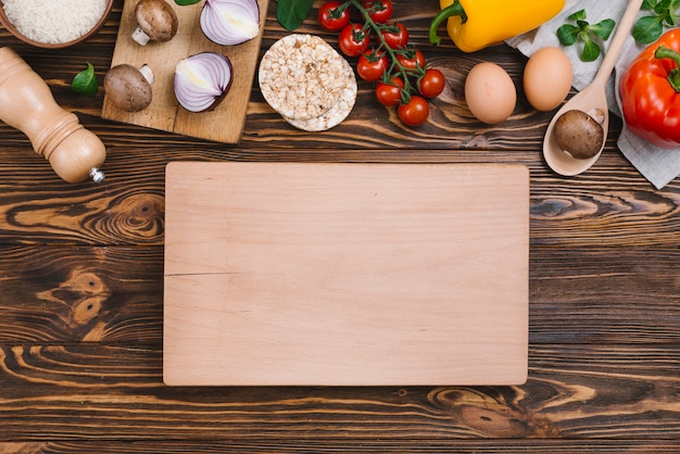 Tabla de cortar de madera en blanco con verduras crudas y pastel de arroz inflado sobre mesa de madera