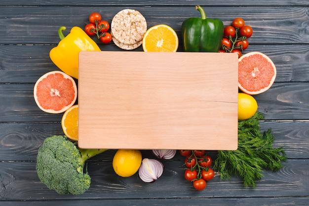 Tabla de cortar de madera debajo de las verduras coloridas en el escritorio de madera negro