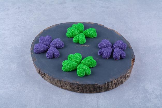 Una tabla de cortar de madera llena de coloridos caramelos de gelatina azucarada
