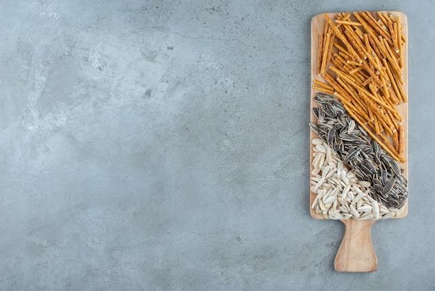 Una tabla de cortar de madera llena de semillas de girasol y palitos de pan. foto de alta calidad