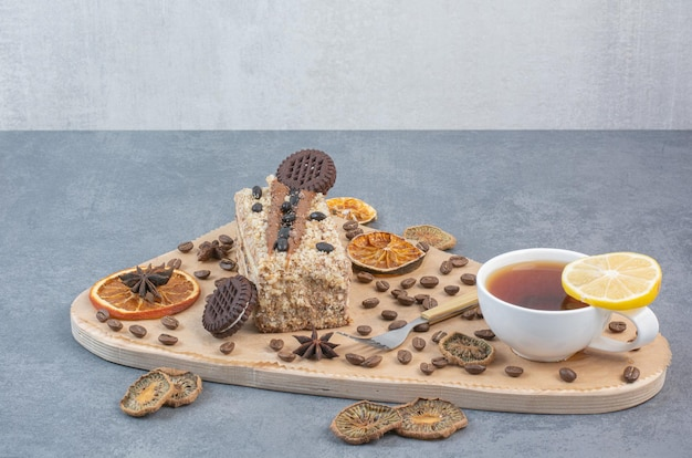 Una tabla de cortar de madera con naranjas secas y granos de café.