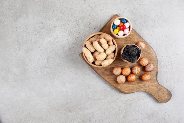 Una tabla de cortar de madera con nueces y moras.