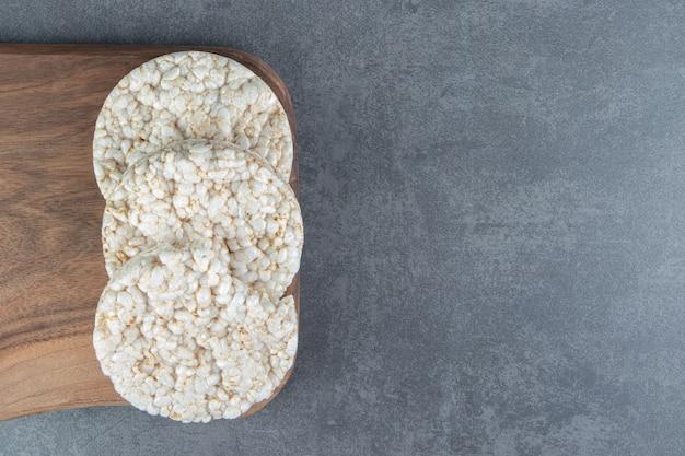 Una tabla de cortar de madera con pan de arroz inflado.